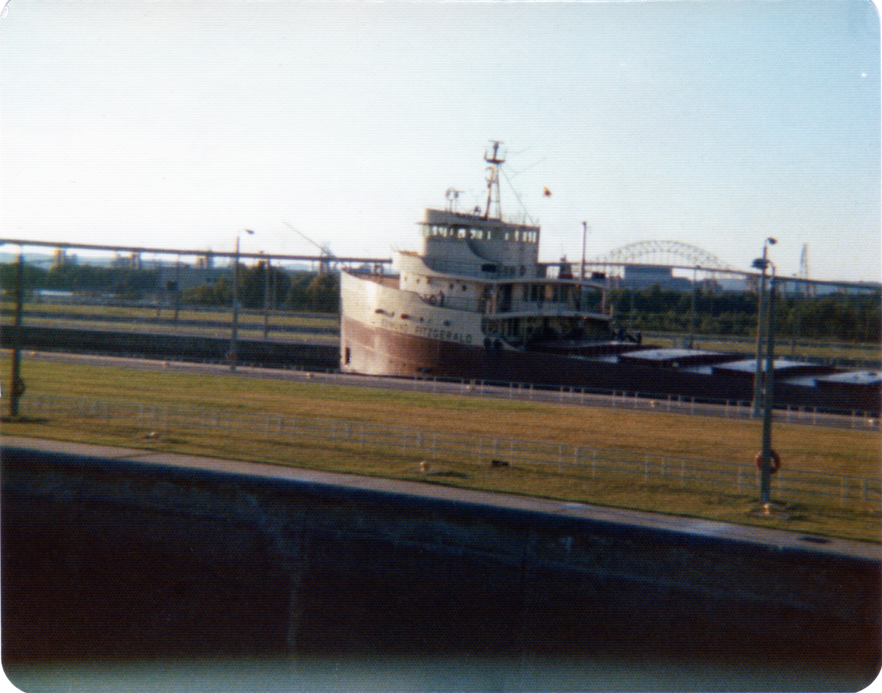 Never before published photo of the Edmund Fitzgerald, taken only months before it was lost with all hands in Lake Superior. Remember, you saw if first on Flickr! My father-in-law took this shot. He told my wife that he wasn't taking a picture of the Big Fitz; he just wanted a photo of the locks, and this happened to be in the photo. Unfortunately, the negative is long gone and this photo was printed on some sort of rough-coated matte paper so that it could be mailed as a postcard. My father-in-law didn't realize until months after the sinking that he had a picture of this vessel. The photo was taken in August 1975; the Edmund Fitgerald sank in November of that year. It was, ironically, the sinking that made this ship famous. After it was built it was the largest ship on the Great Lakes, but other than that, it was just another anonymous working vessel plying the waters between Wisconsin and Michigan.